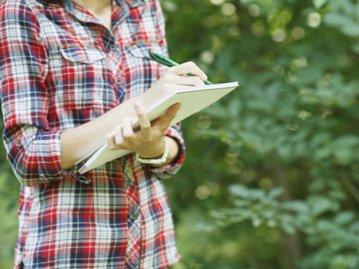 Woman taking notes in a backyard in Ottawa.